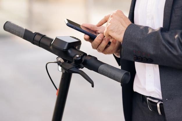 Nierozpoznawalny mężczyzna korzystający z aplikacji na smartfona biznesmen podchodzi do skutera elektrycznego i korzysta z telefonu komórkowego ...