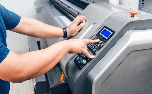 Nierozpoznawalny mężczyzna manipulujący lub kontrolujący przyciski z wielkoformatowej prasy drukarskiej