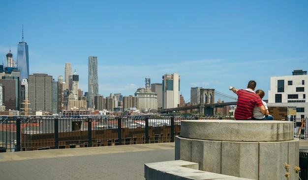 Nierozpoznawalny mężczyzna obejmujący dziecko i pokazujący panoramę manhattanu w nowym jorku