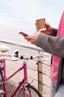 Nierozpoznawalny mężczyzna z drinkiem za pomocą telefonu komórkowego
