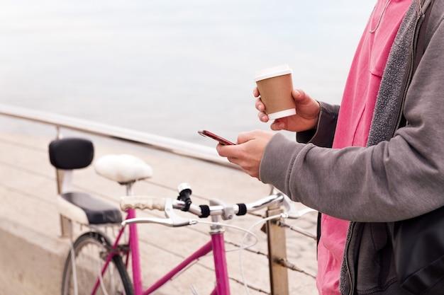 Nierozpoznawalny młody mężczyzna z drinkiem za pomocą telefonu komórkowego obok zabytkowego roweru