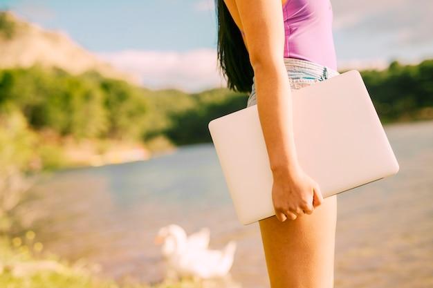 Nierozpoznawalny żeński mienie laptop w malowniczym miejscu
