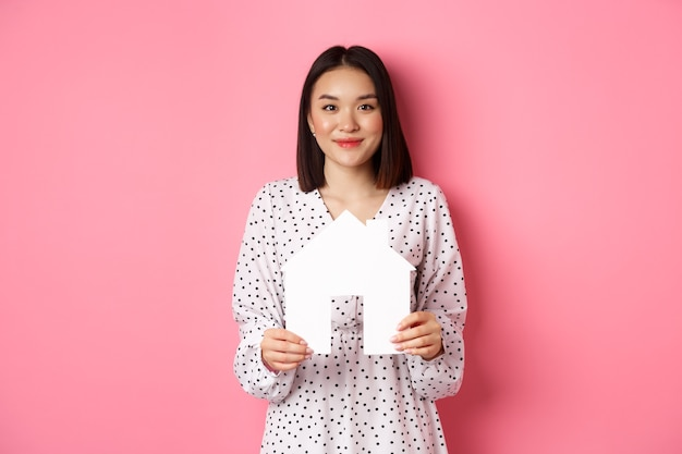 Nieruchomość. dorosła azjatka szuka domu, trzyma model domu i uśmiechnięta, promo firmy brokerskiej, stojąca nad różem