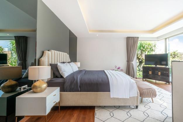 Nieruchomość luksusowy wystrój wnętrz w sypialni willi przy basenie z wygodnym łóżkiem typu king-size.