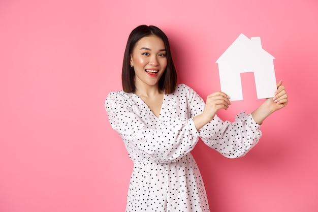 Nieruchomość. piękna azjatycka kobieta demonstruje model domu z papieru, patrząc na kamerę pewna siebie, reklamująca dom na sprzedaż, stojąca nad różem