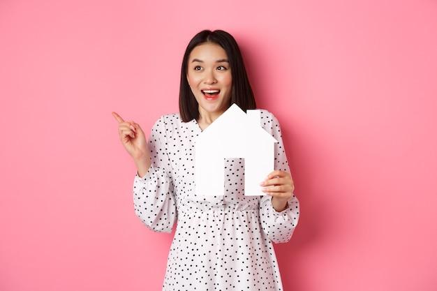 Nieruchomość. podekscytowana azjatycka kobieta pokazująca papierowy model domu, wskazując i patrząc w lewo na miejsce, stojąc na różowym tle
