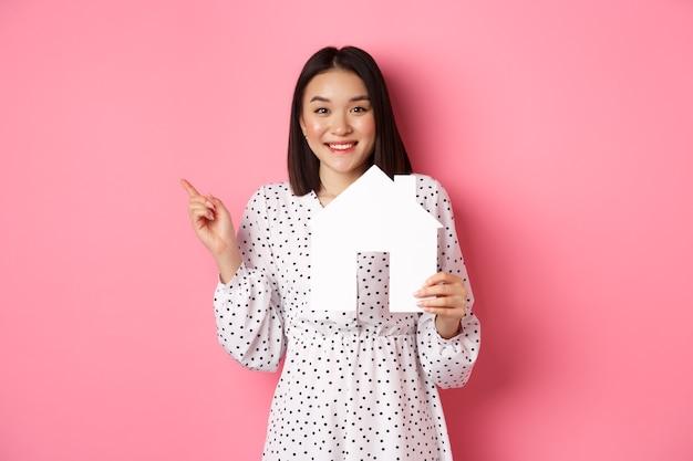 Nieruchomość. podekscytowana azjatycka kobieta pokazująca papierowy model domu, wskazująca w lewo na miejsce na kopię, stojąca nad różem