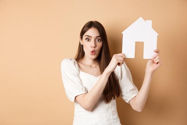"""Nieruchomość. podekscytowana kobieta pokazująca wycinankę z papierowego domu i mówiąca """"wow"""" ze zdumieniem, kupująca nieruchomość, stojąca na beżowym tle."""
