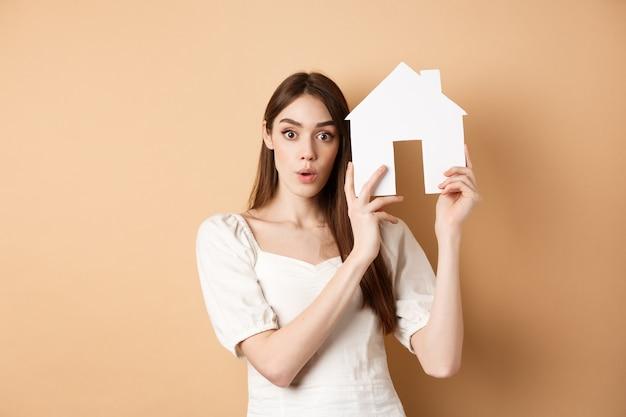 Nieruchomość. podekscytowana młoda kobieta pokazuje wycięcie domu i patrząc na kamery, wynajmując nieruchomość, stojąc na beżowym tle.