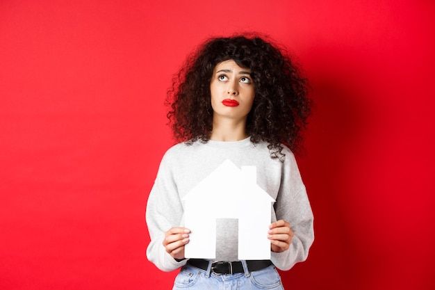 Nieruchomość. smutna kobieta marząca o kupnie mieszkania, trzymająca wycinek z papierowego domu i spoglądająca w górę zmartwiona, stojąca na czerwonej ścianie.