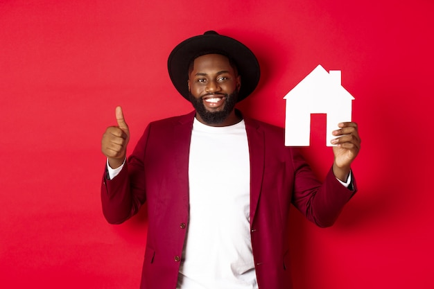 Nieruchomość. stylowy brodaty mężczyzna pokazuje dom maket