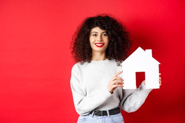 Nieruchomość. uśmiechnięta kaukaska kobieta z kręconymi włosami i czerwonymi ustami, pokazująca papierowy model domu, szukająca nieruchomości, stojąca na czerwonej ścianie.