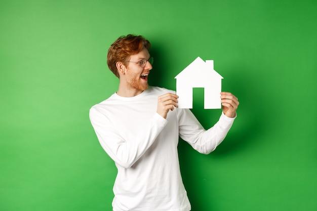 Nieruchomość. wesoły kaukaski mężczyzna z rudymi włosami, patrząc na wycinankę z papierowego domu i uśmiechnięty zdumiony, kupujący nieruchomość, stojący na zielonym tle.