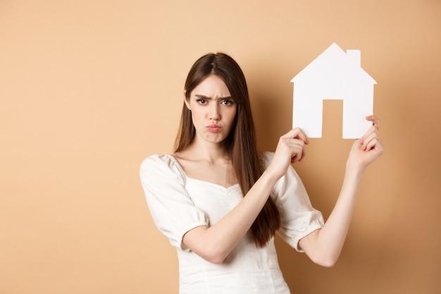 Nieruchomość. wściekła dziewczyna pokazująca wycinek domu i marszcząca brwi, narzekająca na mieszkanie, stojąca na beżowym tle.