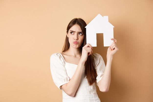 Nieruchomość. zdenerwowana młoda kobieta pokazuje wycinankę z papieru i marszczy brwi, patrzy na bok zamyślony, myśli o zakupie mieszkania, stojąc na beżowym tle.