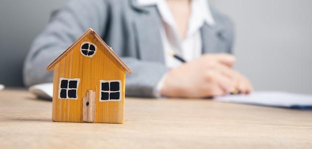 Nieruchomości, kobieta pracująca w dokumencie z modelem domu