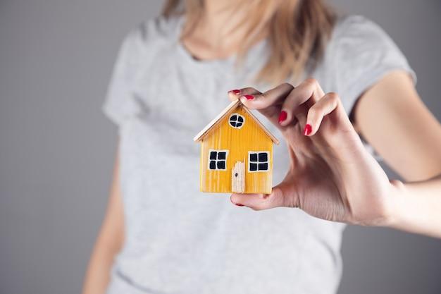 Nieruchomości, kobieta trzyma drewniany model domu