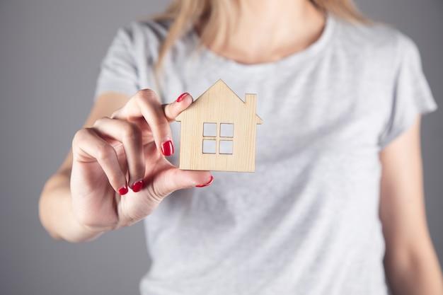 Nieruchomości, Kobieta Trzyma Drewniany Model Domu Premium Zdjęcia