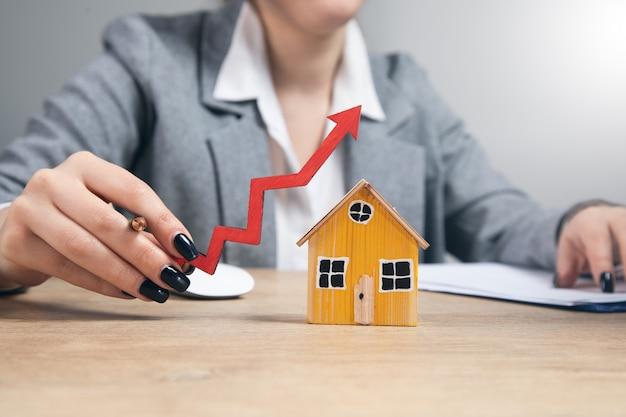 Nieruchomości, kobieta trzyma model domu ze strzałką
