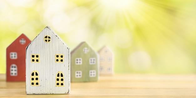 Nieruchomości, koncepcja ubezpieczenia, hipoteka, kupno sprzedam dom. miniaturowe domy na tle przyrody z promieni słonecznych.