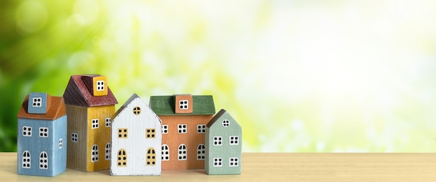 Nieruchomości, kup sprzedam dom, koncepcja hipoteki. miniaturowe domy wiersz na zielonym tle przyrody z promieni słonecznych.