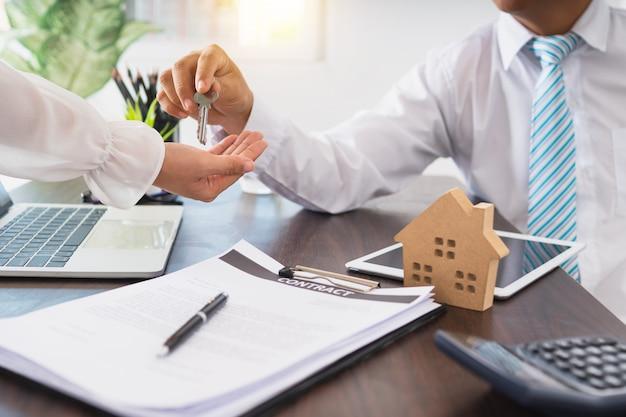 Nieruchomości, makler dom mieszkalny dają klucz do klienta, kupują dom i sprzedają koncepcję domu