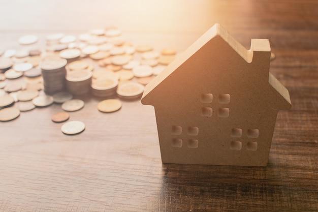 Nieruchomości pojęcie, domu model i monety na drewno stole