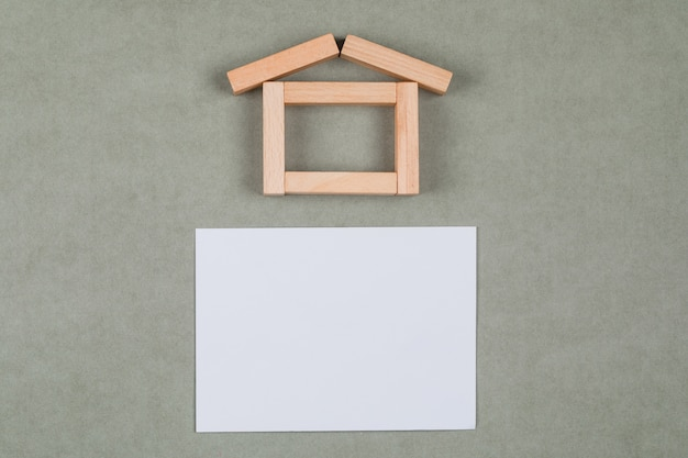 Nieruchomości pojęcie z drewnianymi blokami, kleista notatka na szarym tła mieszkaniu nieatutowym.