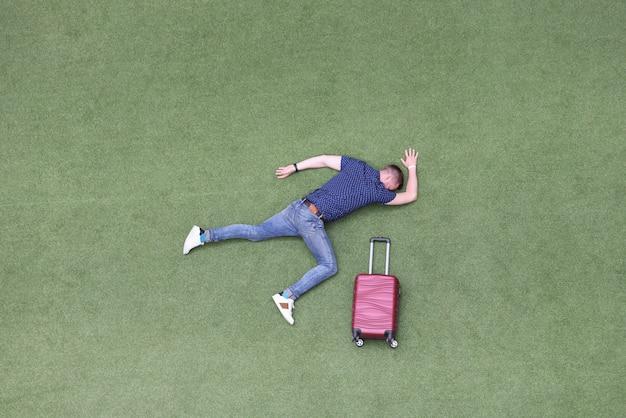 Nieruchomy mężczyzna leży na zielonym trawniku z walizką