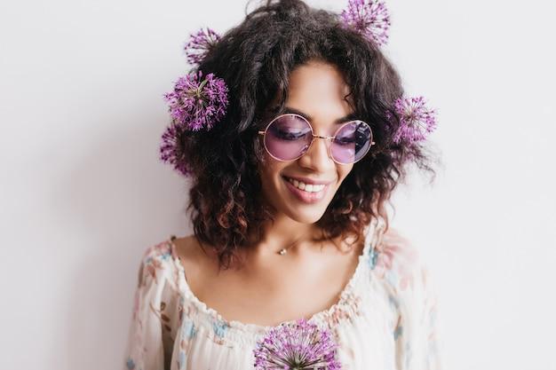 Niesamowita afrykańska dama pozuje z ładnym uśmiechem. portret pięknej czarnej dziewczyny z pięknymi fioletowymi kwiatami.