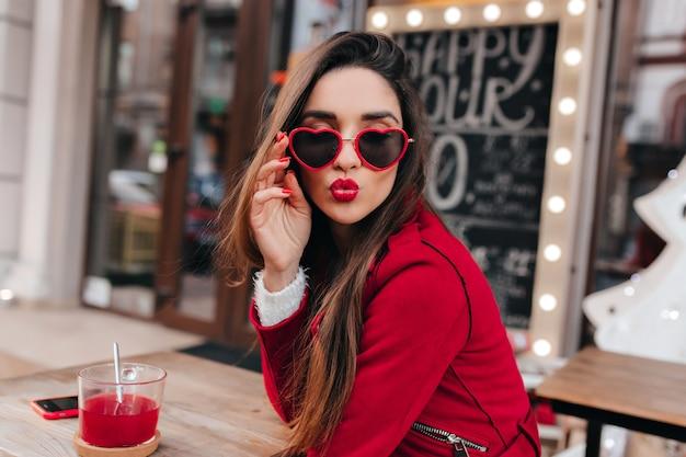 Niesamowita biała dziewczyna w modnych okularach serca pozuje z całującą miną