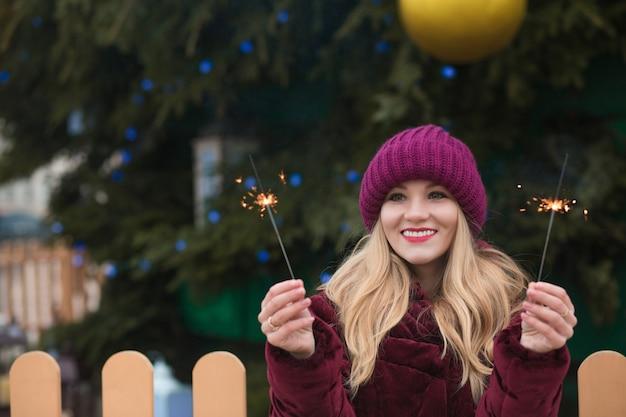 Niesamowita blondynka bawi się błyszczącymi światłami bengalskimi na świerku noworocznym w kijowie