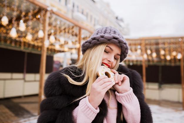 Niesamowita blondynka w czapce z dzianiny, jedząca smaczne świąteczne pierniki na jasnym tle