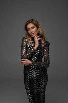 Niesamowita blondynka z długimi kręconymi fryzurami i naturalnym makijażem w studio dla magazynu o modzie. ubrana w czarną imprezową sukienkę z błyszczącymi elementami i butami na wysokim obcasie. profesjonalna modelka, wspaniała pani