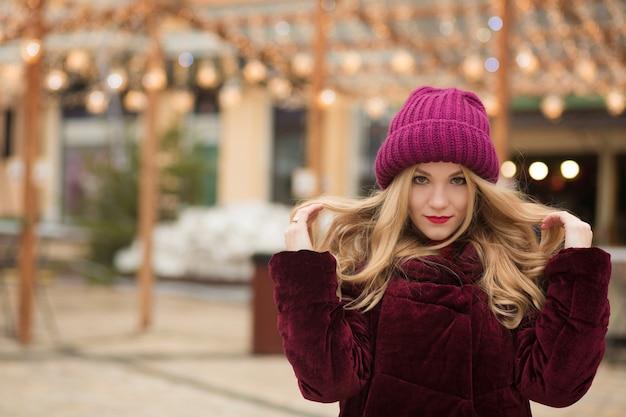 Niesamowita blondynka z długimi włosami pozuje na tle girlandy na ulicy w kijowie