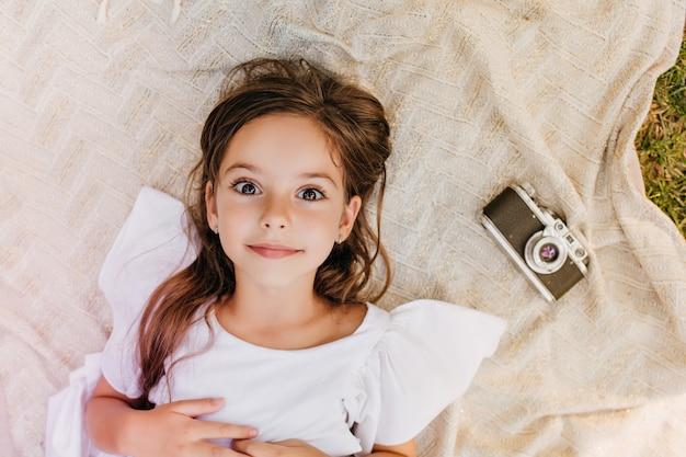Niesamowita ciemnooka dziewczyna leżąca na kocu z zaskoczonym uśmiechem obok aparatu. ogólny odkryty portret małej damy w białej sukni, relaks na trawie w parku.