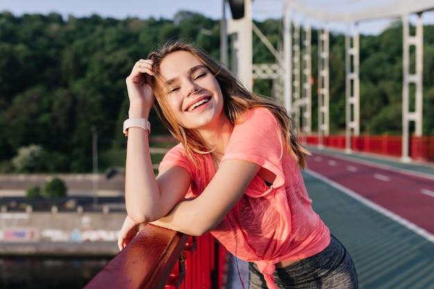 Niesamowita ciemnowłosa dziewczyna śmiejąca się po treningu. odkryty strzał szczęśliwa biała dama spędza poranek na stadionie.