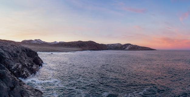 Niesamowita czarna żwirowa plaża na wybrzeżu morza barentsa w pobliżu teriberki. widok panoramiczny. zima na półwyspie kolskim, obwód murmański, rosja.