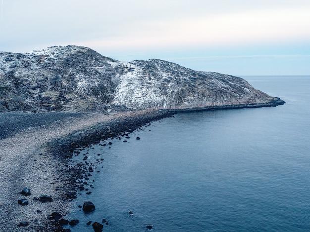 Niesamowita czarna żwirowa plaża na wybrzeżu morza barentsa w pobliżu teriberki