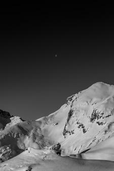 Niesamowita czarno-biała fotografia pięknych gór i wzgórz z ciemnym niebem