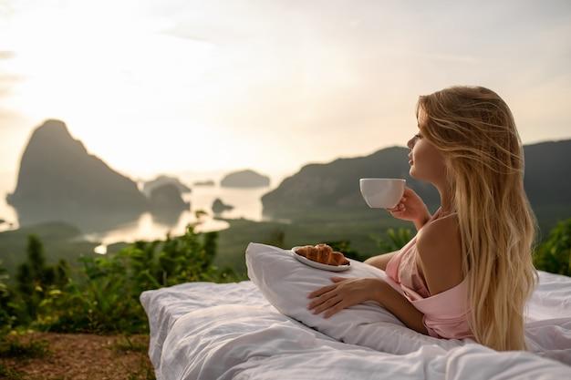 Niesamowita czuła dziewczyna pozuje na łóżku z kawą i rogalikami