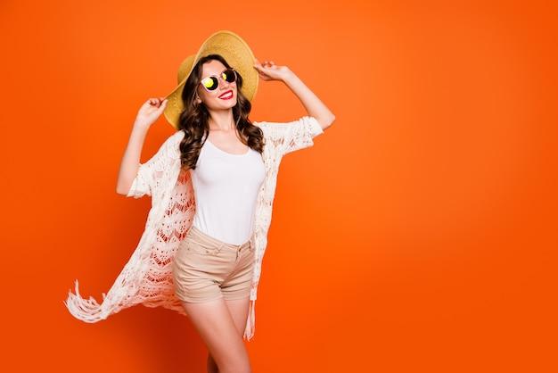 Niesamowita dama pozuje z kapeluszem i letnimi ubraniami, koncepcja wakacji letnich