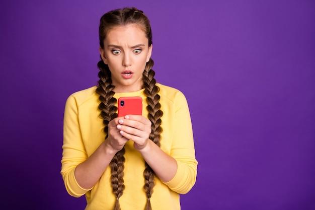 Niesamowita dama z długimi warkoczami trzymająca telefon czytająca okropne wiadomości oniemiały blog startowy epicki niepowodzenie nosić swobodny żółty sweter na białym tle fioletowy kolor ściany