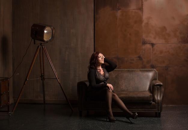 Niesamowita dojrzała brunetka w modnym stroju pozuje na skórzanej sofie w ciemnym pokoju