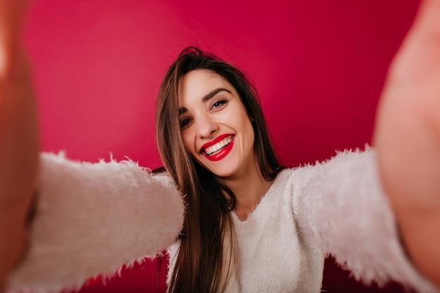 Niesamowita dziewczyna w puszystym swetrze wyrażającym radość