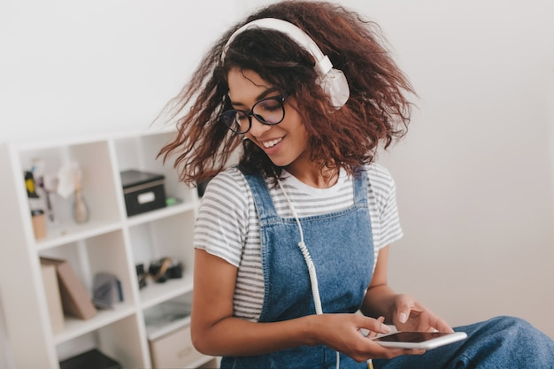 Niesamowita dziewczyna z ciemnobrązowymi kręconymi włosami bawi się w biurze przy słuchaniu muzyki w białych słuchawkach