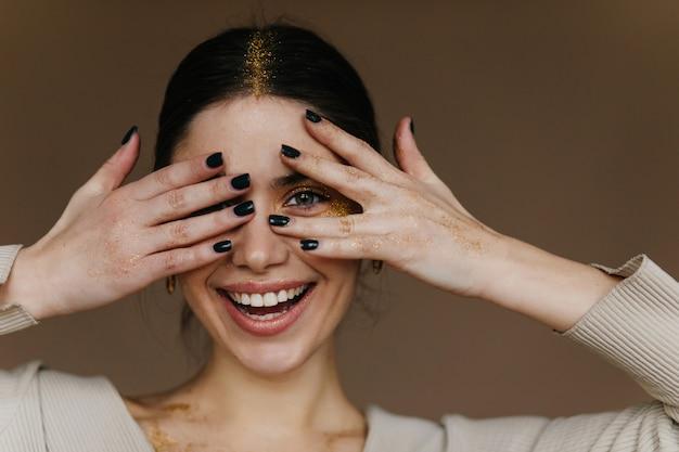 Niesamowita dziewczyna z makijażem strony pozuje z radosnym uśmiechem. szczegół portret zadowolony młoda dama z czarnymi włosami.