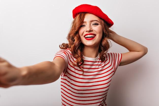 Niesamowita europejska dziewczyna w czerwonym berecie śmiejąca się pozytywna francuska młoda kobieta robi selfie.