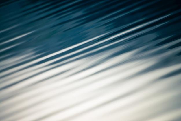 Niesamowita faktura spokojnej niebieskiej powierzchni czystej wody. światło słoneczne w halnym jeziornym zakończeniu. piękne fale na błyszczącej wodzie w słoneczny dzień. cudowna relaksująca konsystencja.