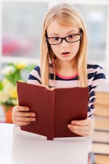 Niesamowita historia! zaskoczona mała dziewczynka czyta książkę siedząc przy stole